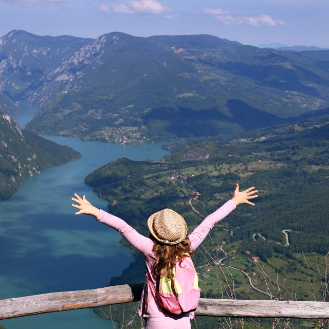 """""""little girl hiker with hands up on mountain viewpoint"""" stock image"""
