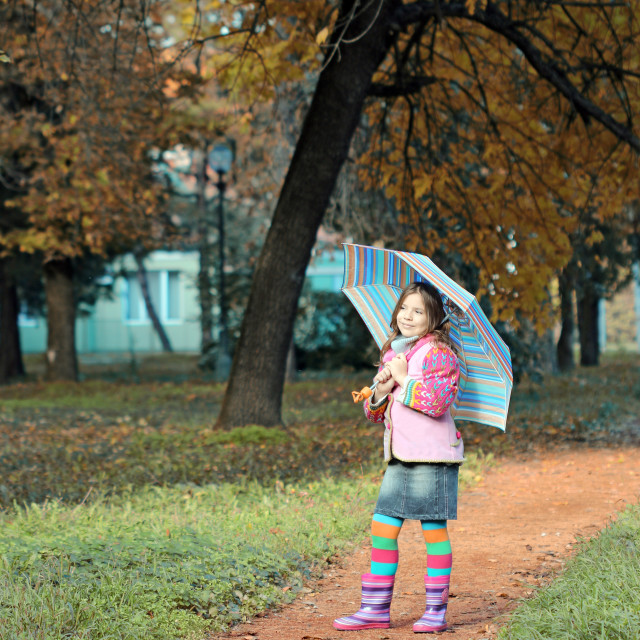"""little girl with umbrella in park autumn season"" stock image"