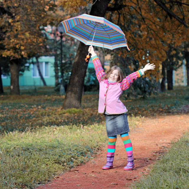 """Happy little girl with umbrella in park autumn season"" stock image"