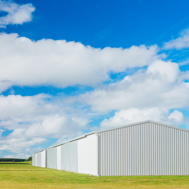 """Metallic warehouse with blue sky"" stock image"
