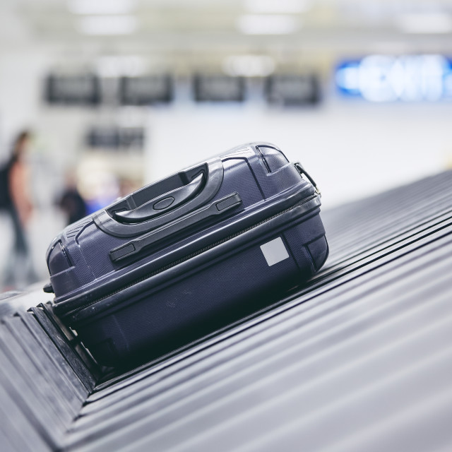 """Suitcase on baggage claim"" stock image"