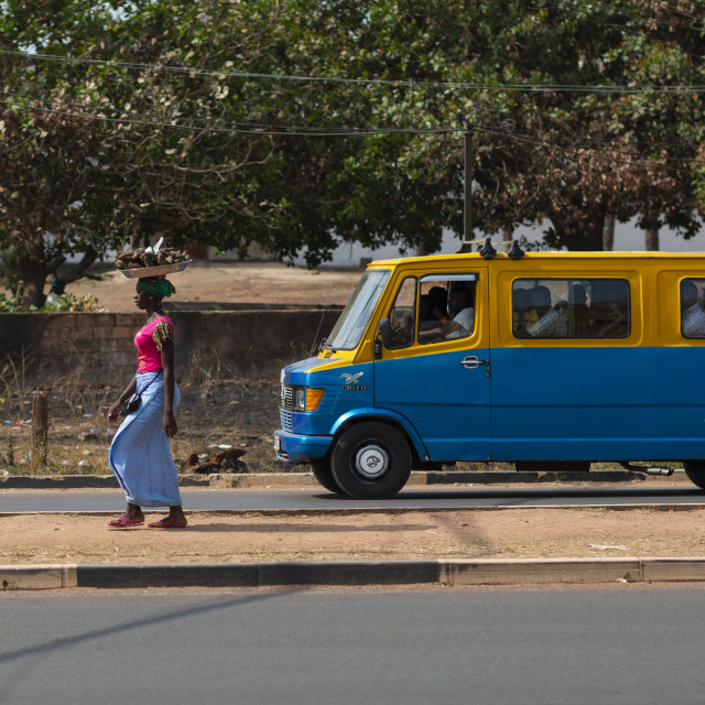 """Bissau, Republic of Guinea-Bissau - January 31, 2018: Street scene in the city of Bissau with a woman carrying a tray on her head and a public bus (toca toca) in Guinea-Bissau, West Africa"" stock image"