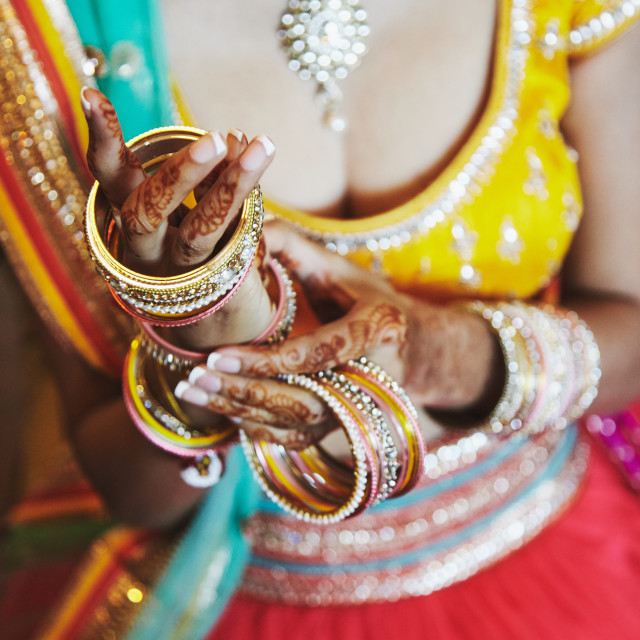 """""""Indian bride wear saree putting the bracelets (bangle) on hand with mehndi, close-up"""" stock image"""
