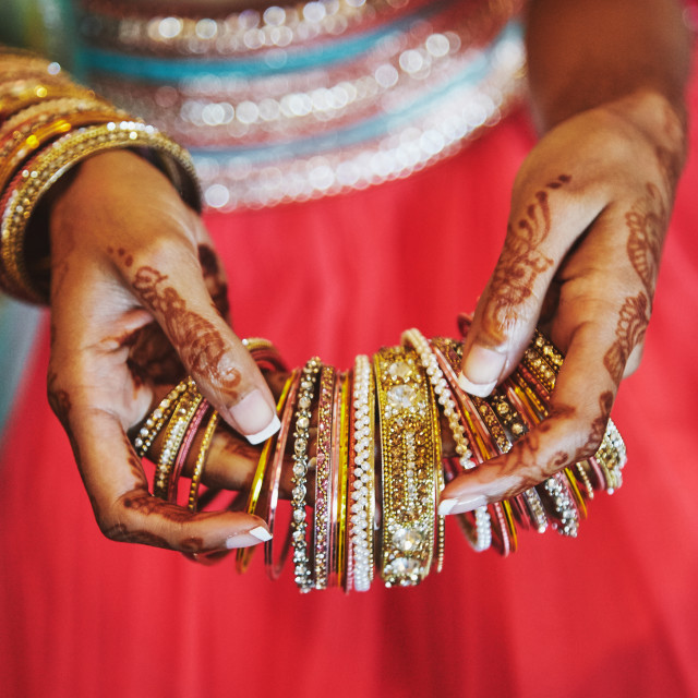 """""""The hand with mehndi of Indian bride holding a lot of glitter bracelets (bangle) with red legenha background, close-up"""" stock image"""