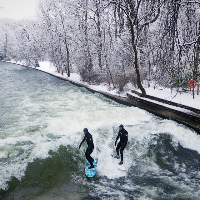 """""""MUNICH, GERMANY - surfers riding the artificial wave on the Eisbach in winter"""" stock image"""