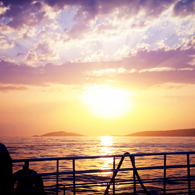 """""""Man on a ferry looking at sunset"""" stock image"""