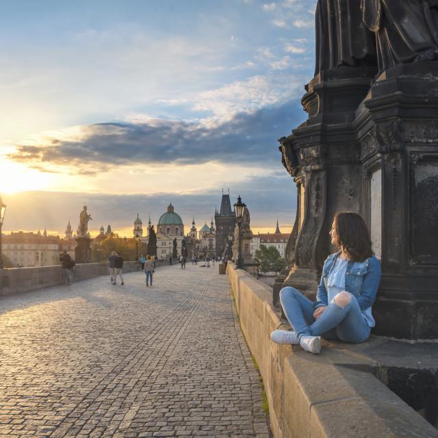 """Girl watching the sunrise on Charles Bridge"" stock image"