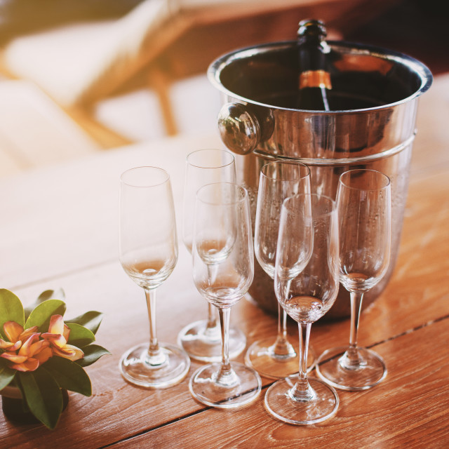 """A set of champagne glasses with ice bucket of champagne bottle on the wooden table with warm lighting from left side"" stock image"