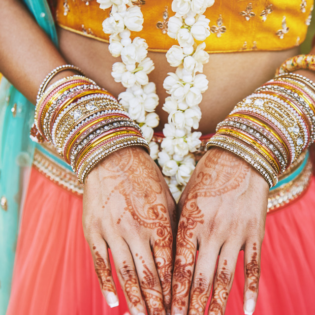 """Indian bride showing menhdi (henna) tattoo on hand with bunch of glitter bangles on her wrist, close-up"" stock image"