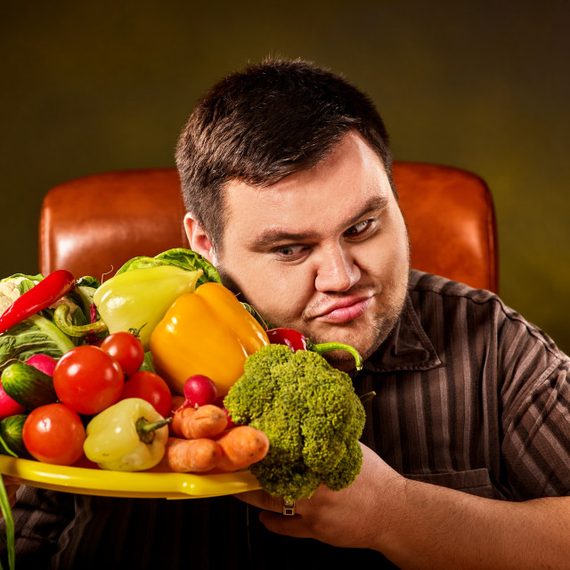 """Diet fat man eating healthy food. Healthy breakfast with vegetables."" stock image"