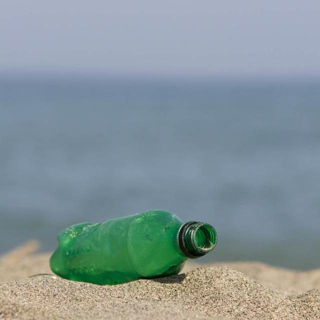 """Empty plastic bottle left behind on beach"" stock image"