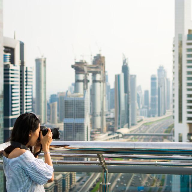 """Photographer taking picture of Dubai cityscape"" stock image"