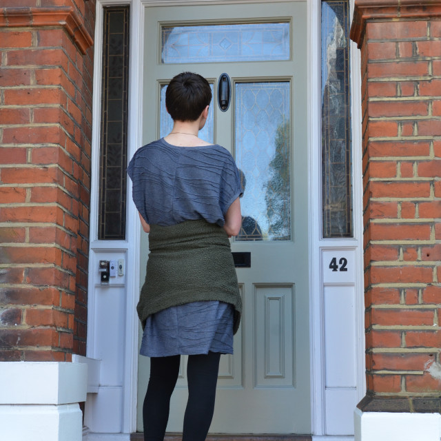 """Canvasser knocking on a green door and waiting outside"" stock image"