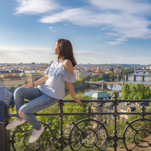 """""""Woman on a fence and panorama of Prague City"""" stock image"""