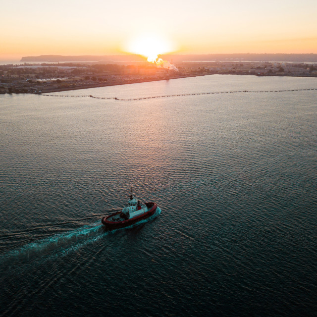 """Aerial photo of a small tugboat at sunset"" stock image"
