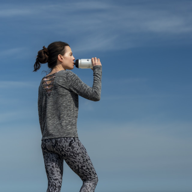 """""""sporty woman standing by the sea resting and drinking from a sports water bottle"""" stock image"""