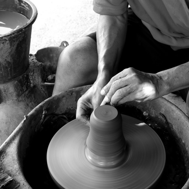 """A craftsman finalizes a cup on a pottery wheel - Square format"" stock image"