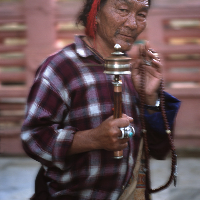 """Man with prayer wheel, Bodh Gaya"" stock image"
