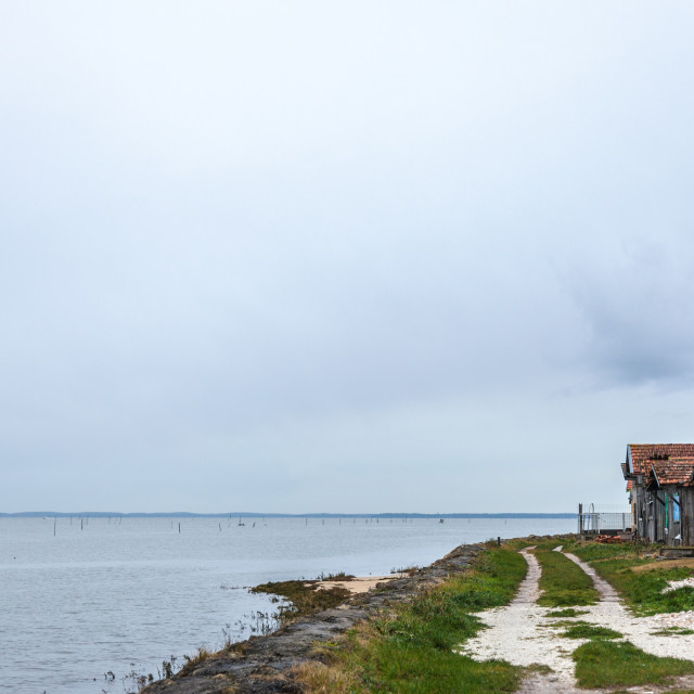 """""""Oyster farmers huts near the Atlantic ocean during a cloudy rainy afternoon..."""" stock image"""