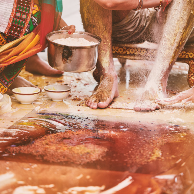 """""""Family members pasting the turmeric powder (haldi) oil mixed with milk on groom's feet and body"""" stock image"""