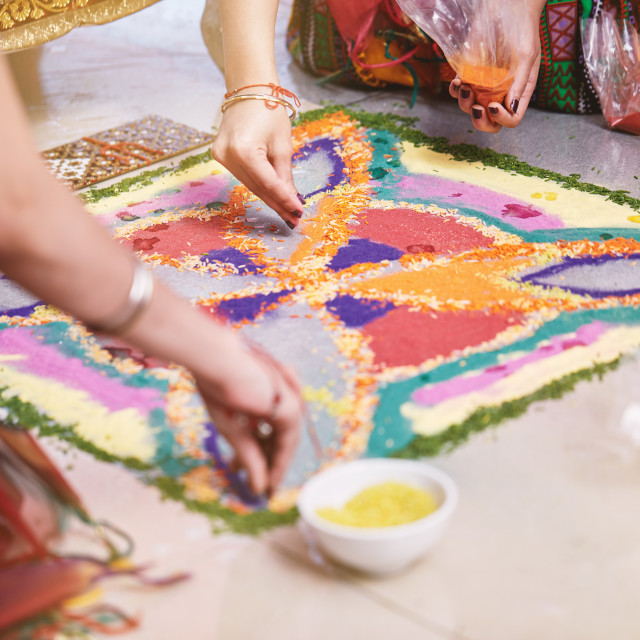 """""""Bride's friend helps coloring the traditional rice art (Rangoli) on the floor for indian wedding"""" stock image"""