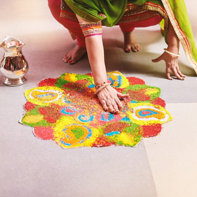 """""""Women coloring traditional rice art (Rangoli) for indian marriage rituals"""" stock image"""