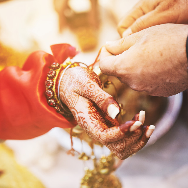 """""""Indian bride ties with holy thread on her wrist at ceremony focus on hand with blurry background"""" stock image"""