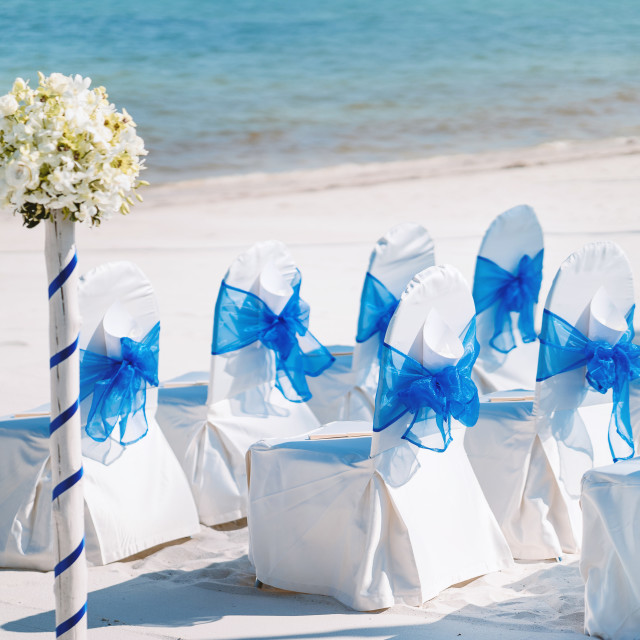 """A group of white spandex chairs cover with blue organza sash for beach wedding venue setup"" stock image"