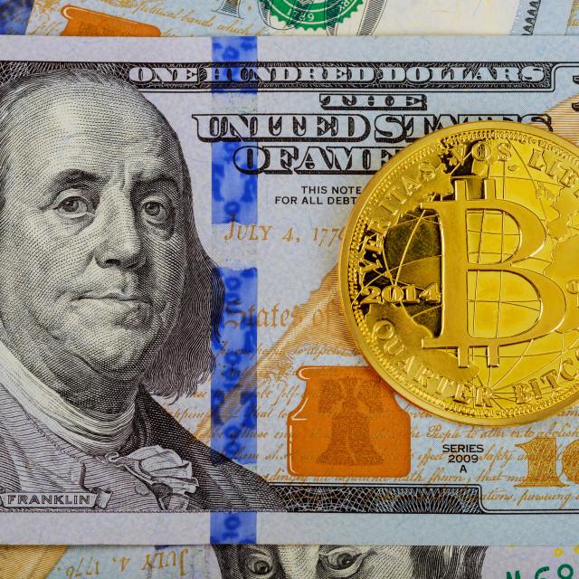 """Gold Bitcoin on hundred dollars bills. Close-up, macro shot."" stock image"