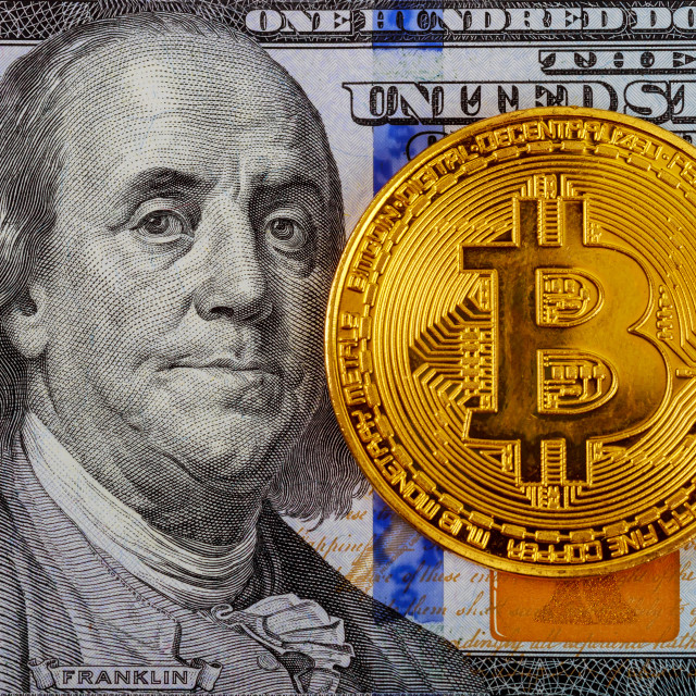 """Golden Bitcoins on US dollars. Digital currency close-up. New virtual money. Crypto currency top view. Real coins of bitcoin on banknotes of one hundred dollars."" stock image"