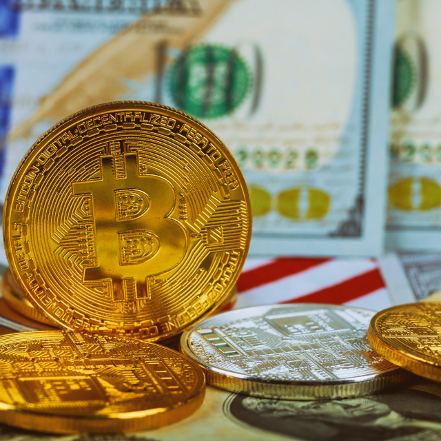 """The concept of the value of the crypto currency. golden bitcoin coin on us dollars close up"" stock image"