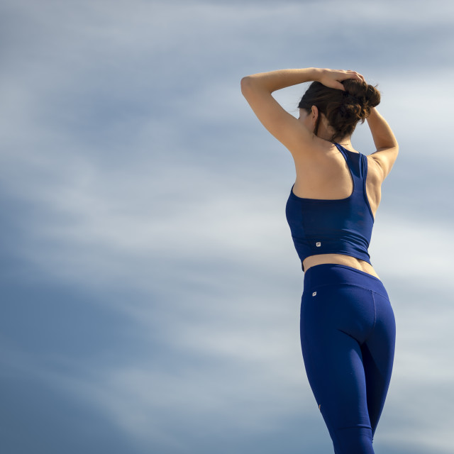 """""""back view of a woman wearing sportswear adjusting her hair before exercising"""" stock image"""