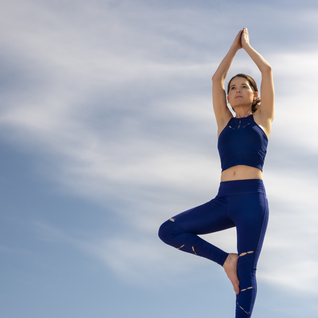 """""""woman practicing yoga, doing a tree pose outside in the summer with a blue sky."""" stock image"""