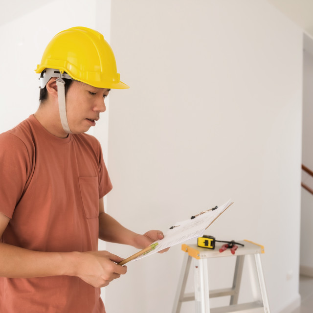 """Interior engineer with new house blueprint"" stock image"
