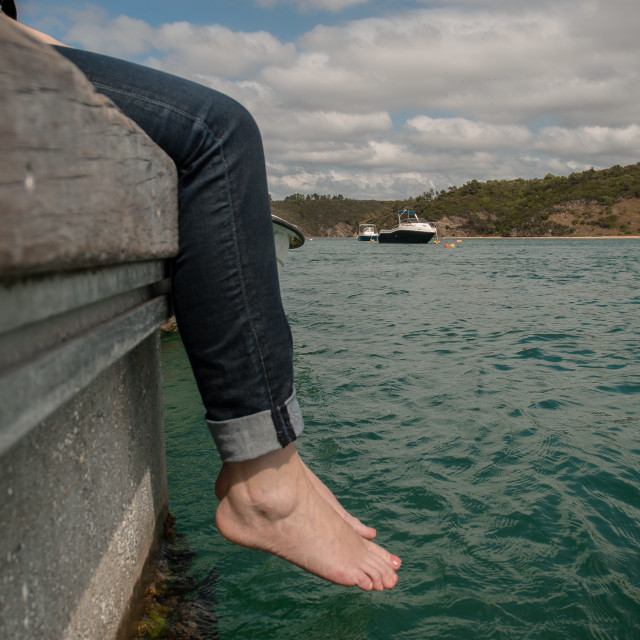 """Barefoot Girl sitting on pier"" stock image"