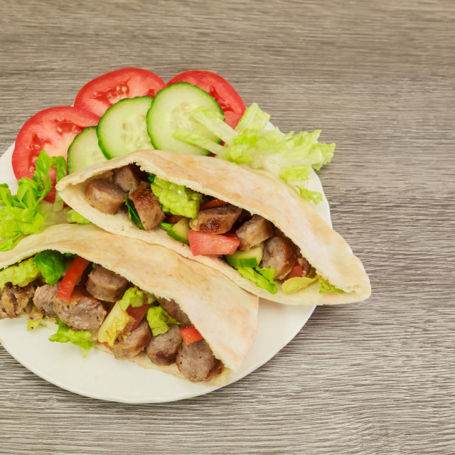 """""""Falafel and fresh vegetables in pita bread on wooden"""" stock image"""