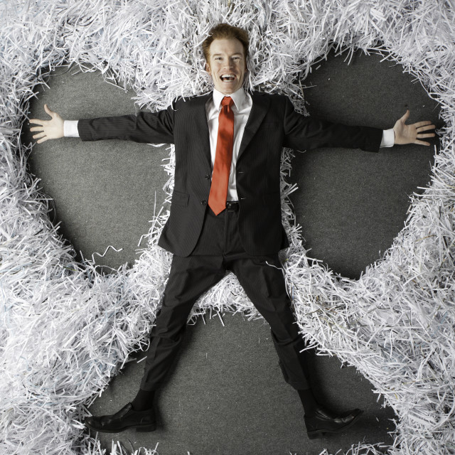 """Executive doing snow angel in shredded paper"" stock image"