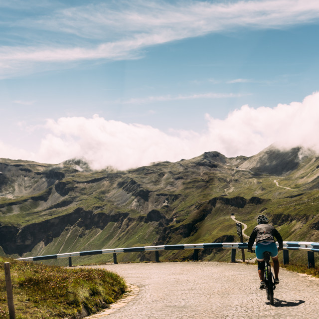 """""""Rear view of woman riding bicycle on mountain road"""" stock image"""