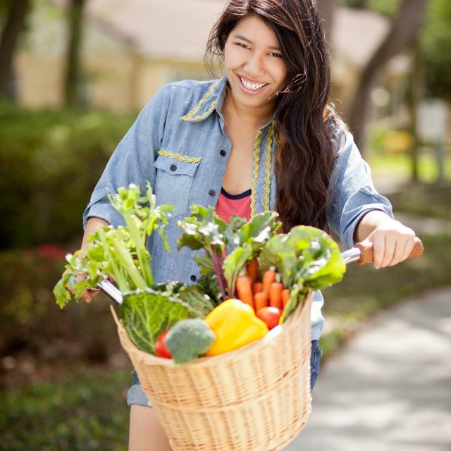 """Young female riding bike with basket full of vegetables"" stock image"