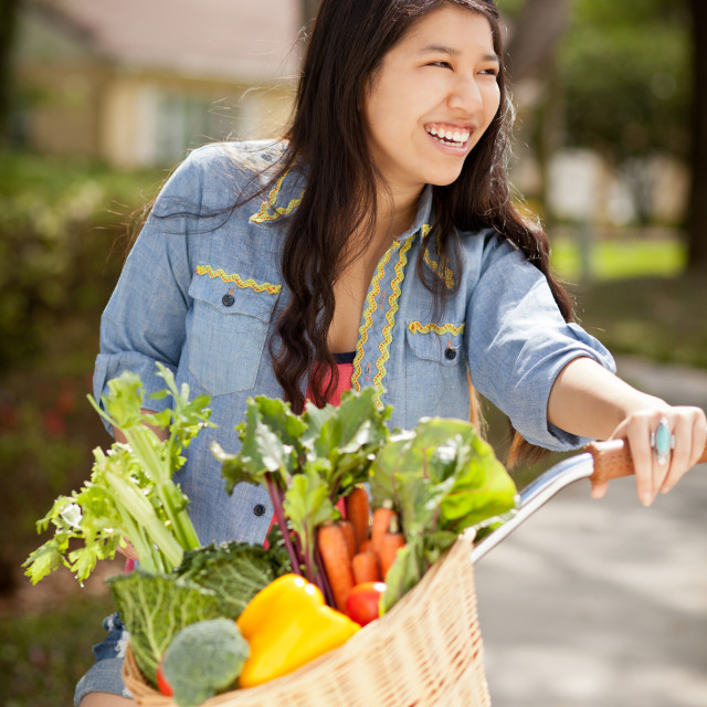 """""""Young female riding bike with basket full of vegetables"""" stock image"""