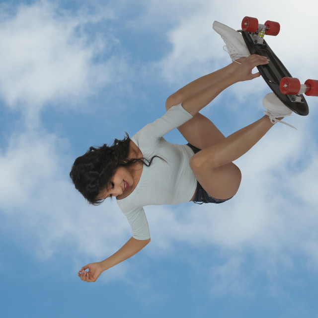 """Woman riding skateboard"" stock image"