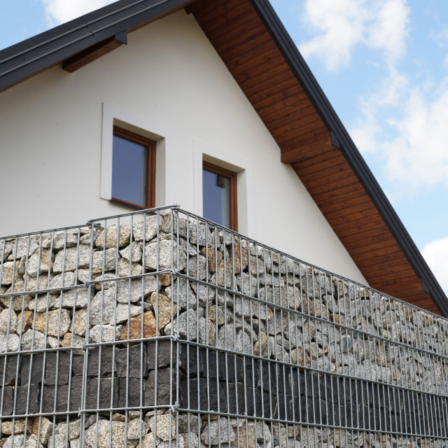 """A house surrounded by a modular gabion fence"" stock image"