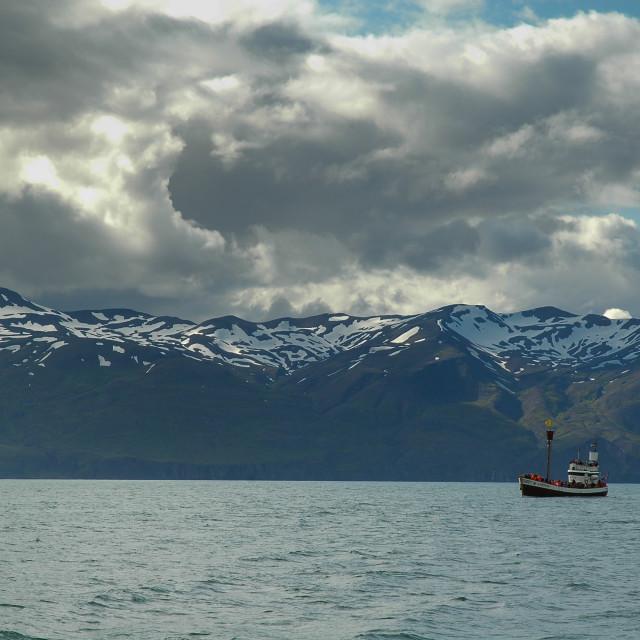 """Boat at sea with snowcapped mountains beneath"" stock image"