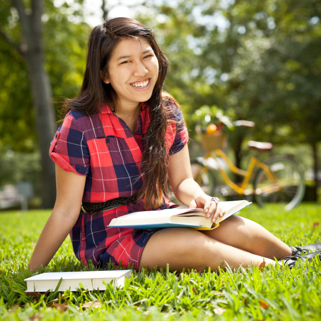 """""""young female reading book in park"""" stock image"""