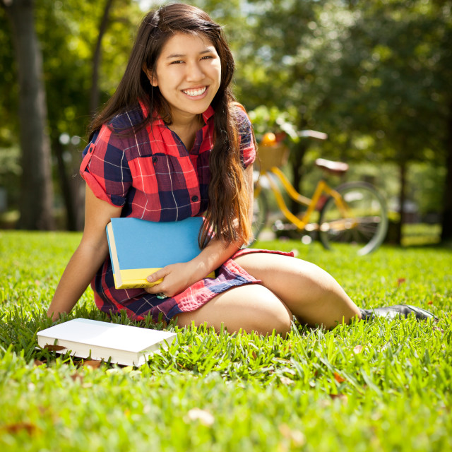 """young female reading book in park"" stock image"