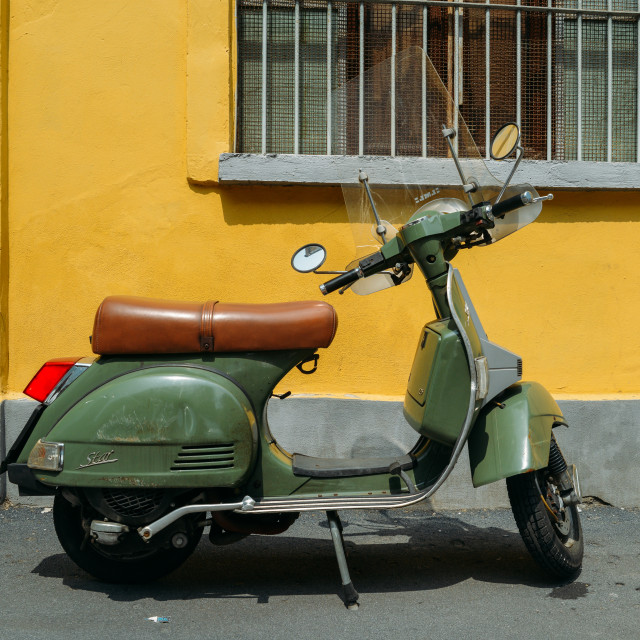 """Green Piaggio Vespa LML T5 150 parked on side of street with yellow background"" stock image"