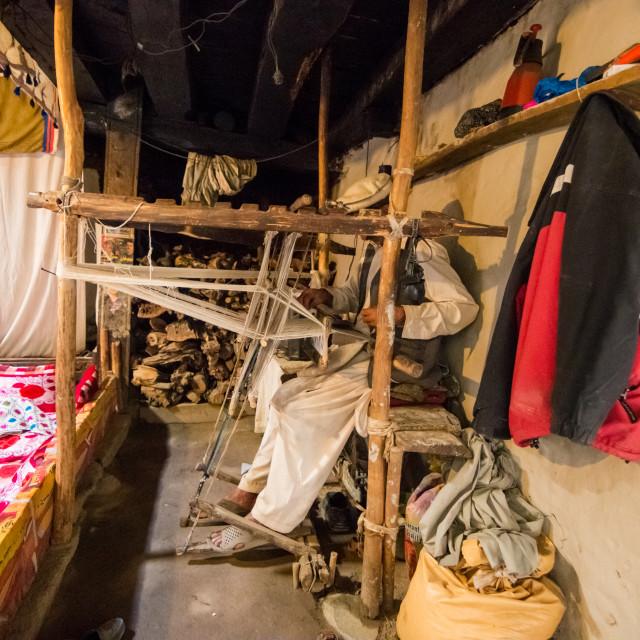 """A man dressed like an afghan weave a carpet on a handmade weaving loom"" stock image"