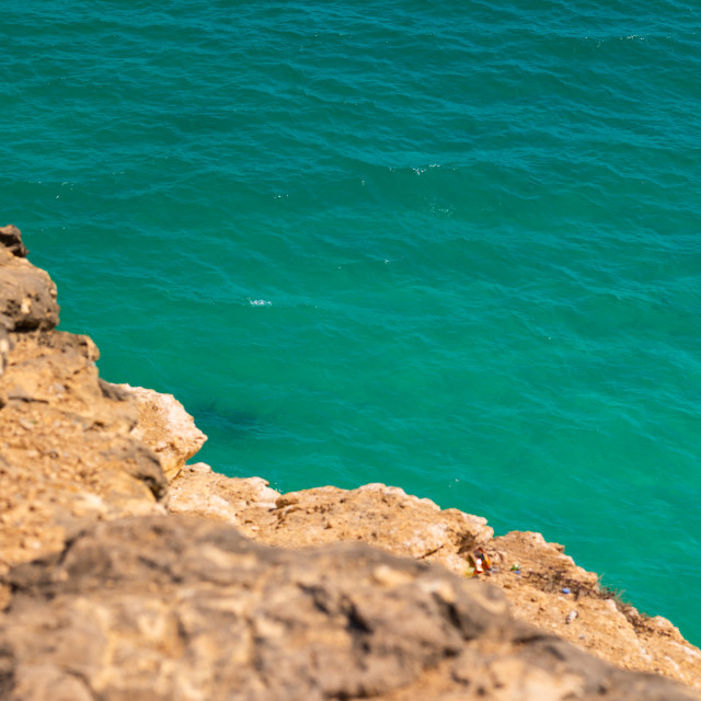 """""""Cliff over the green water, Dhofar Governorate, Taqah, Oman"""" stock image"""