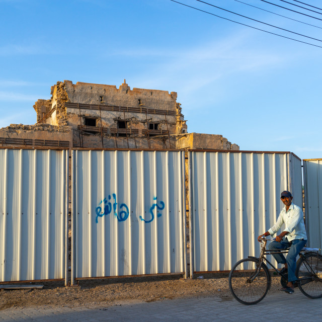 """Indian man passing in front of the old palace protected by a fence, Dhofar..."" stock image"