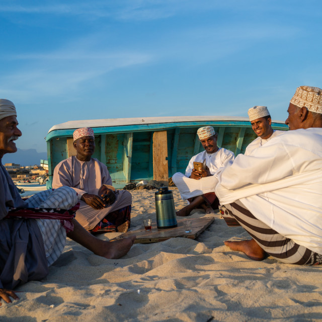 """Omani men resting and drinking tea on the beach at sunset, Dhofar..."" stock image"